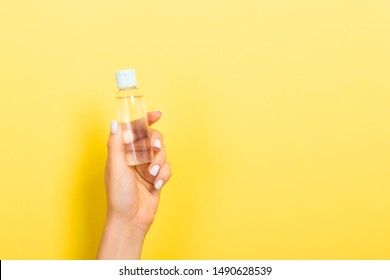 Female hand holding cream bottle of lotion isolated. Girl give jar cosmetic products on yellow background.