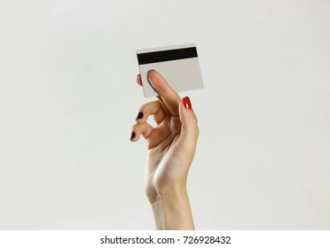 Female hand holding credit card. Isolated on gray background. Closeup.