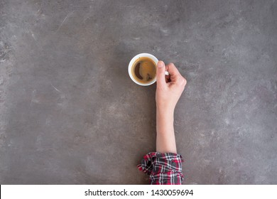 Female hand holding a cup of americano coffee. Love coffee concept background with copy space.
