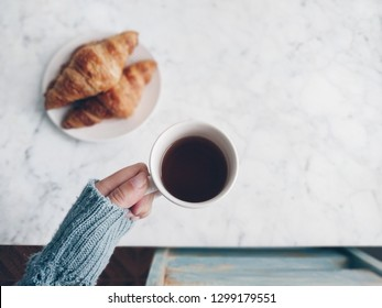 female hand holding a cup of coffee and croissants on marble table