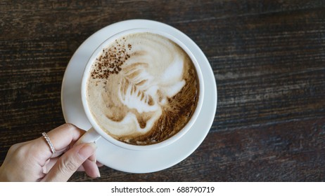 Female hand holding a cup of coffee with foam over wooden table background, top view