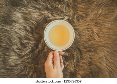 Female hand holding a cup of green tea on the fluffy brown fur plaid. Flat lay, top view, vintage colors, copy space.