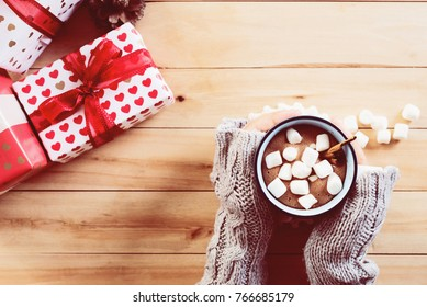 female hand holding cup of hot cocoa or chocolate with marshmallow on wooden table from above