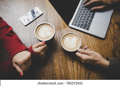 Female hand holding cup of hot latte coffee and mobile phone with friend working on laptop at coffeeshop, co working space concept