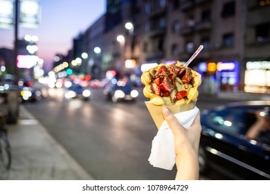 Female hand holding a dessert crepes with a defocused urban background