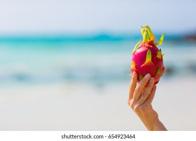 Female hand holding a dragon fruit on blue sea background