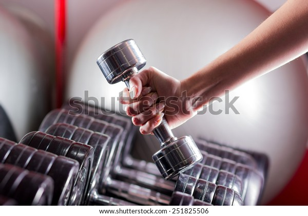 Female hand holding a dumbbell in gym. Sport background.