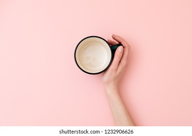 Female hand holding empty mug on pink background. Flat lay, top view, overhead