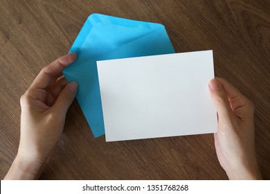 A female hand holding an envelope and post card on wooden background