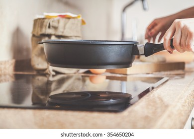Female hand holding a frying pan over a smooth surface electric stove