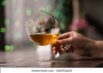 Female hand holding glass of cognac. Relaxation concept. Snifter of brandy in elegant glass with space for text. Strong alcoholic drink.