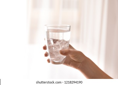 Female hand holding glass with fresh water on light background