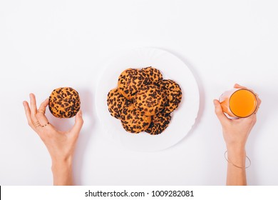 Female hand holding a glass of juice and cookies top view