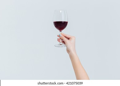 Female hand holding glass with wine isolated on a white background