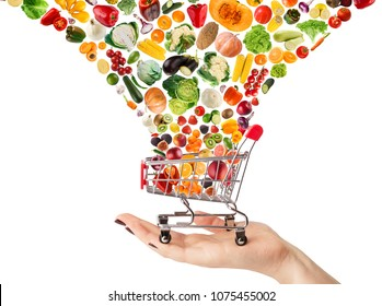 Female hand holding grocery cart with vegetables and fruits falling in it isolated on white. Healthy meals shopping, cornucopia and wellbeing concept. Collage of brignt food and trolley, cutout