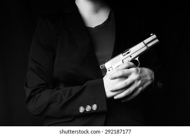 female hand holding gun with a black background