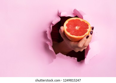 Female hand holding half of grapefruit through torn pink paper background. Fresh orange juice. Vegan, vegetarian concept. Copy space.