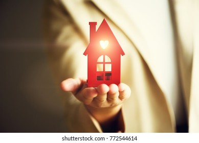 Female hand holding house key, real estate agent. Property insurance, security and cozy home concept. Copy space.