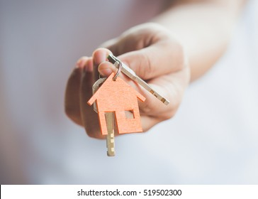 Photo of Female hand holding house key,real estate agent.
