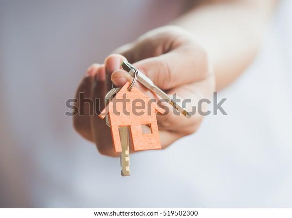 Vrouwelijke hand met huissleutel, makelaar.