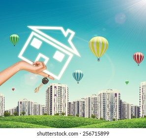 Female hand holding icon house and keys. Green hills with high-rise buildings and sky with air balloons in background