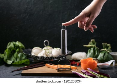 Female hand holding Julienne Peeler. Chinese style dumplings with chives served with traditional Japanese onigiri, soy sauce, sweet chili sauce and decorated with banana leaves and chili peppers