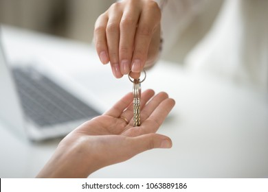 Female hand holding key, woman getting real estate ownership, customer buying new lease rental house becoming first time home owner, property purchase, mortgage investment loan concept, close up view