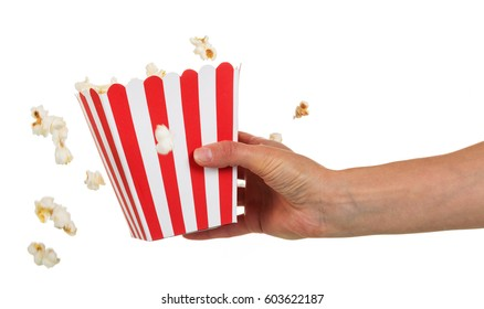 A female hand holding a large square box of popcorn and popcorn falling out of it isolated on white background.