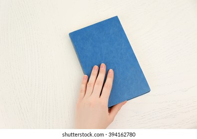 Female hand holding a light-blue book cover  on white desk, top view