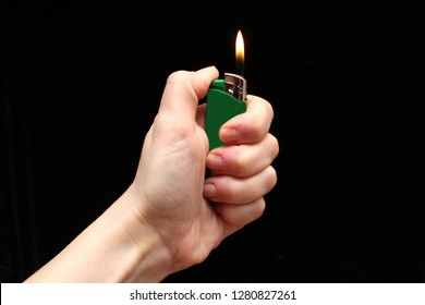 Female hand holding a lighter with a burning flame on a black background