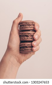 The female hand holding macaroons on grey background, close-up