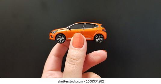 female hand holding metal car toy exact model of orange color on black background