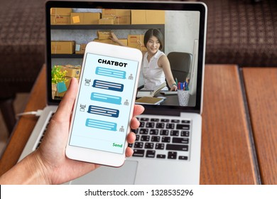 Female hand holding mobile phone showing the chatbot message While Young asian teenager owner business woman working and prepaing package the product at home for online shopping, entrepreneur concept