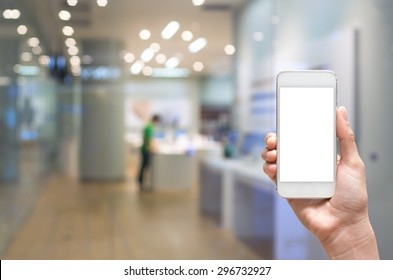 Female hand holding mobile smart phone on store blur with bokeh background, business concept