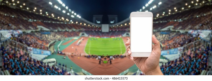 Female hand holding mobile smart phone touch screen on Panorama of Abstract blurred photo of fan sport at stadium, sport background concept