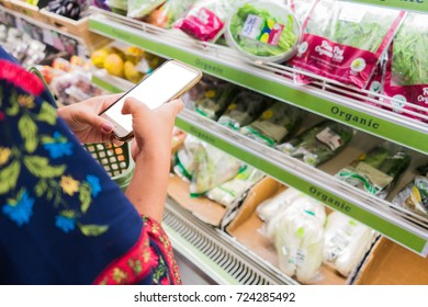 Female hand holding mobile smart phone on Supermarket business concept