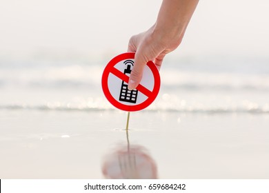 "Female hand holding ""No phone calls"" sign on the beach"