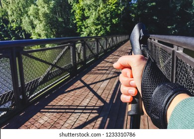 Female hand holding Nordic walking pole on bridge across river. Concept of healthy lifestyle. Point of view shot