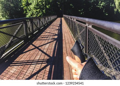 Female hand holding Nordic walking pole on bridge. Concept of healthy lifestyle. Point of view shot