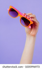 Female hand holding orange eyeglasses on purple background