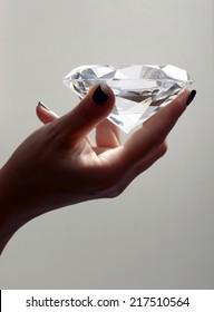 Female Hand Holding Over sized Illuminated Diamond in Studio with Grey Background