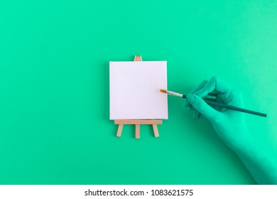 Female hand holding paintbrush and small easel for artists with blank canvas. Green color minimal creative concept. Space for copy.
