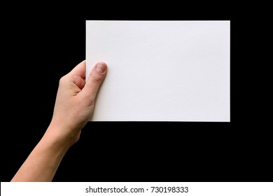 Female hand holding paper blank isolated on black