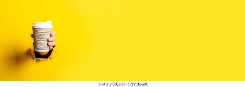 Female hand holding a paper cup of coffee with the lid closed on a bright yellow background. Banner.