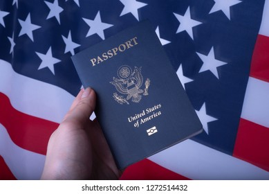 Female hand holding Passport of USA on American glag background.
