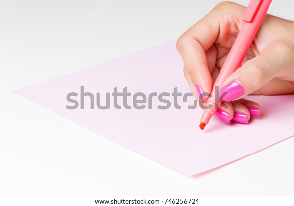 Female hand holding a pen close up