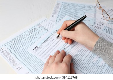 Female hand holding a pen next to the metal rimmed glasses and filling in the 1040 Individual Income Tax Return Form for 2015 year on the white desk, close up