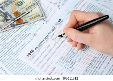 Female hand holding a pen next to the metal rimmed glasses and dollar bills while filling in the 1040 Individual Income Tax Return Form for 2015 year on the white wooden desk, close up