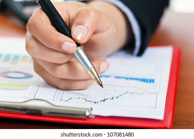 Female hand holding a pen while studying a financial chart