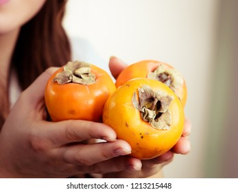 Female hand holding persimmon kaki fruits. Healthy eating, aid in weight loss, improve digestion.
